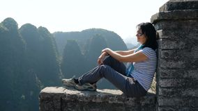 Woman on the edge of the cliff. Attractive woman sitting on the edge of the cliff against high rocky mountains, admiring beautiful views of from above at Tam Coc stock footage