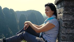 Woman on the edge of the cliff. Attractive woman sitting on the edge of the cliff against high rocky mountains, admiring beautiful views of from above at Tam Coc stock video footage