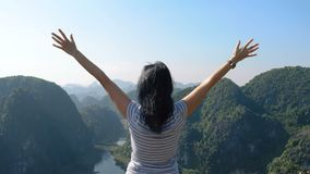 Woman on the edge of the cliff raising her hands. Attractive woman standing on the edge of the cliff and raising her hands up against high rocky mountains stock video footage