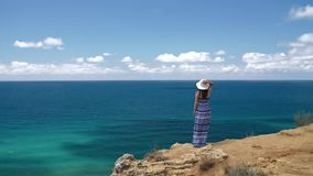 Woman at the edge of the cliff. Woman wearing dress and hat at the edge of the cliff watching seascape stock video