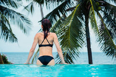 Woman on the edge of an infinity pool by the ocean Royalty Free Stock Photo