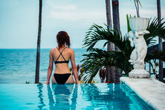 Woman on the edge of an infinity pool by the ocean Stock Photo