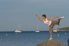 Woman at the edge of the sea. Woman making a exercise of balance at the seaside Stock Images