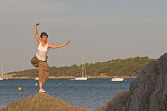 Woman at the edge of the sea. Woman making a exercise of balance at the seaside Royalty Free Stock Image