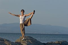 Woman at the edge of the sea. Woman making a exercise of balance at the seaside Stock Image