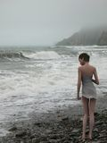 Woman on edge of the stormy sea Royalty Free Stock Photo