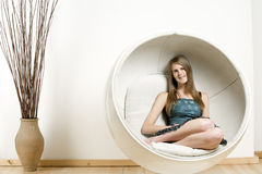 Woman in Egg style chair Royalty Free Stock Photo