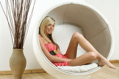 Woman in Egg style chair Royalty Free Stock Images
