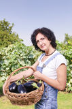 Woman with eggplant in basket Royalty Free Stock Images