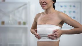 Woman in elasto-fit breast compression touching wrap, feeling pain after surgery. Stock footage stock footage