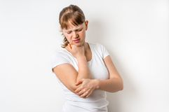Woman with elbow pain is holding her aching arm Royalty Free Stock Image