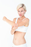 Woman with elbow pain looking at camera. On white background Royalty Free Stock Photos