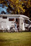 Woman on electric bike resting at the campsite. Family vacation travel, holiday trip in motorhome, Caravan car Vacation royalty free stock photo