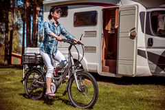 Woman on electric bike resting at the campsite. Family vacation travel, holiday trip in motorhome, Caravan car Vacation royalty free stock images