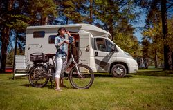 Woman on electric bike resting at the campsite VR Caravan car Va. Woman on electric bike resting at the campsite. Family vacation travel, holiday trip in stock photography