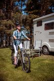 Woman on electric bike resting at the campsite VR Caravan car Va. Woman on electric bike resting at the campsite. Family vacation travel, holiday trip in royalty free stock images