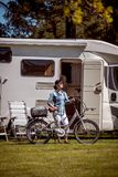 Woman on electric bike resting at the campsite VR Caravan car Va. Woman on electric bike resting at the campsite. Family vacation travel, holiday trip in stock images