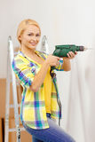 Woman with electric drill making hole in wall Royalty Free Stock Image