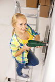 Woman with electric drill making hole in wall Royalty Free Stock Images