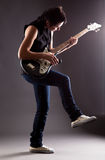 Woman with electric guitar. On gray background Royalty Free Stock Photos