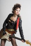 Woman with electric guitar. Beautiful woman playing electric guitar. Shot in studio Stock Photo