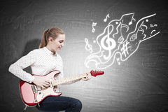 Woman with an electric guitar near a chalkboard with note sketch Royalty Free Stock Photos