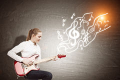 Woman with an electric guitar near a chalkboard with note sketch Royalty Free Stock Images