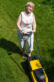 Woman with an electric mower at the cottage Stock Image