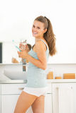 Woman with electric toothbrush in bathroom Royalty Free Stock Photos