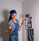 Woman with an electrical box, mallet and hammer Royalty Free Stock Photos