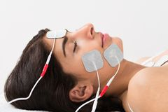 Woman with electrodes on her face Royalty Free Stock Images