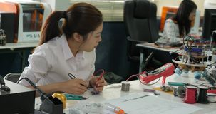 Woman electronics engineer is measuring the signal in the electrical circuit in her workshop. Girl student are studying electronics in classroom stock footage