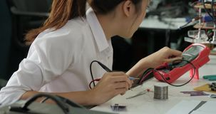 Woman electronics engineer is measuring the signal in the electrical circuit in her workshop. Girl student are studying electronics in classroom stock video