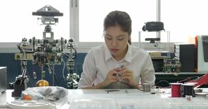 Woman electronics engineer is measuring the signal in the electrical circuit in her workshop. Girl student are studying electronics in classroom stock video footage