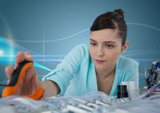 Woman with electronics and pliers against blue background with waves Stock Image