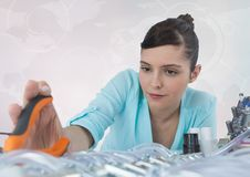 Woman with electronics and pliers against white background with interface Stock Photos