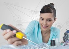 Woman with electronics and screwdriver against white background with graphs Stock Photography