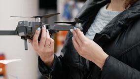 Woman in the electronics store chooses gray drone. She carefully examines the quadcopter before buying. On the background of gadgets and accessories. Gender stock video