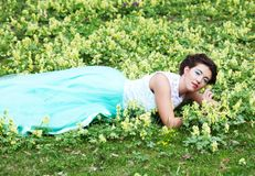 Woman in elegance dress lies on the Grass Royalty Free Stock Photo