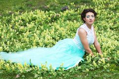 Woman in elegance dress lies on the Grass Royalty Free Stock Images