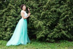 Woman in elegance dress posing in the garden. Stock Image