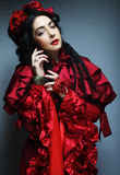 Woman in elegance red costume with red hat. Royalty Free Stock Image