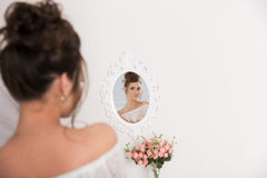 Woman in elegance underwear looks at the mirror Royalty Free Stock Photos