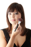 Woman in elegant black dress does a make up Stock Photos