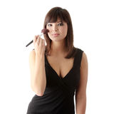 Woman in elegant black dress does a make up Royalty Free Stock Image