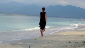 Woman in elegant black dress walking down beautiful beach stock video footage