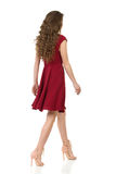 Woman In Elegant Burgundy Dress Is Walking. Side Rear View. Royalty Free Stock Photo