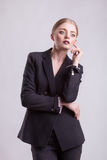 Woman in elegant business suit on grey background Royalty Free Stock Images