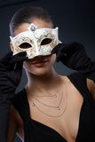 Woman in elegant carnival mask. Woman in elegant black dress hiding in decorated carnival mask, seductive smile Royalty Free Stock Images