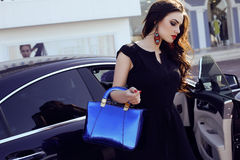 Woman in elegant dress with bag, posing beside a luxurious auto Stock Images